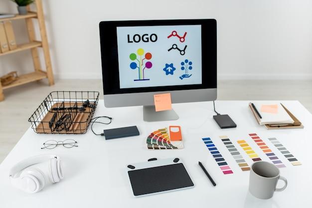 Компьютерный монитор с логотипом на экране, графический планшет со стилусом, кружка, палитра и другие вещи на столе