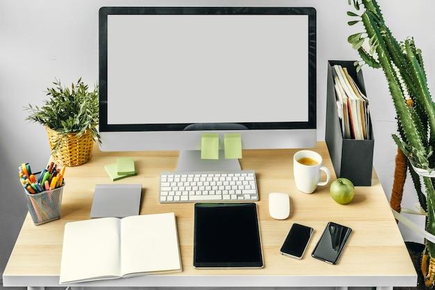 Монитор компьютера с макетом белого экрана на офисном столе с принадлежностями