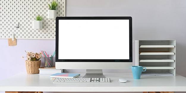 白い作業机の上に置く白い空白の画面とコンピューターモニター