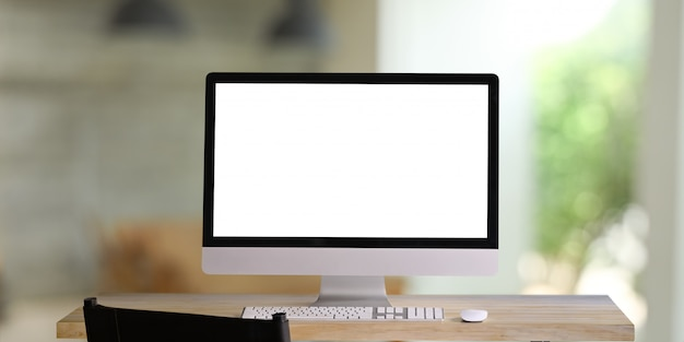 Computer monitor with white blank screen putting on workspace wooden desk with keyboard and mouse.