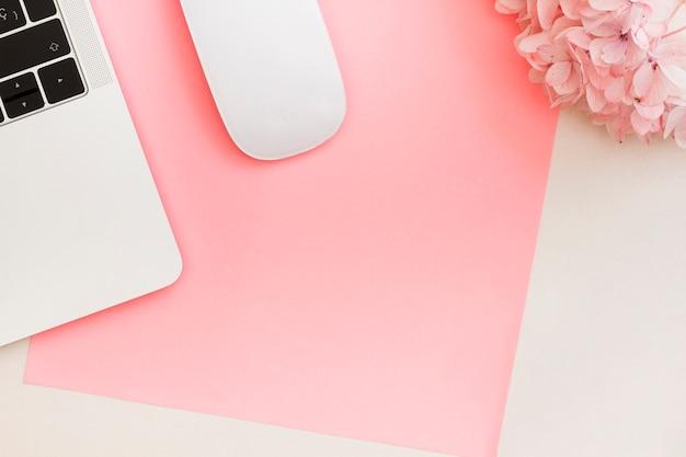コンピューターのマウスとノートパソコンの花の横に