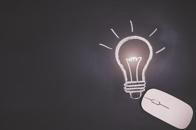 コンピューターのマウスの概念、黒板の電球のシンボルはアイデアを表しています