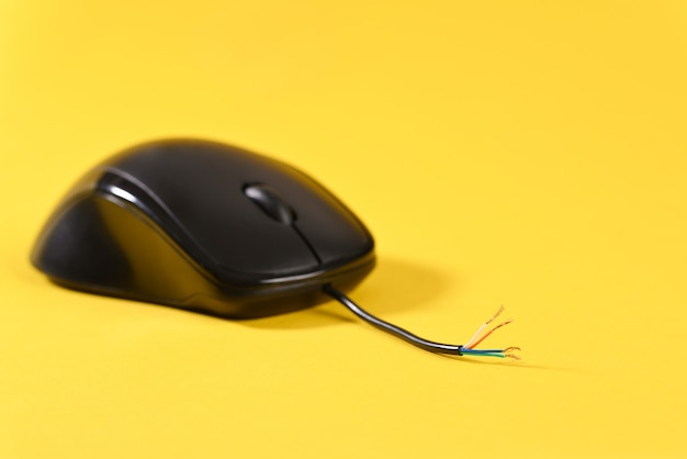 Компьютерная мышь со сломанным кабелем на желтом фоне