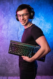 Computer nerd with keyboard over colorful pink and blue neon lit wall