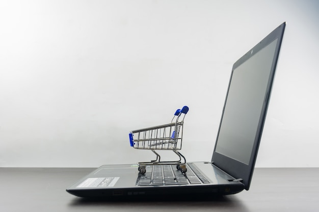 Computer notebook blank screen with shopping cart on wood table