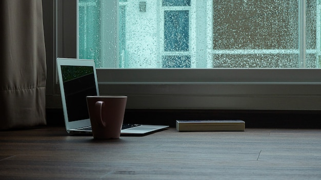 Computer notebook next to a cup coffee on rainy day window background