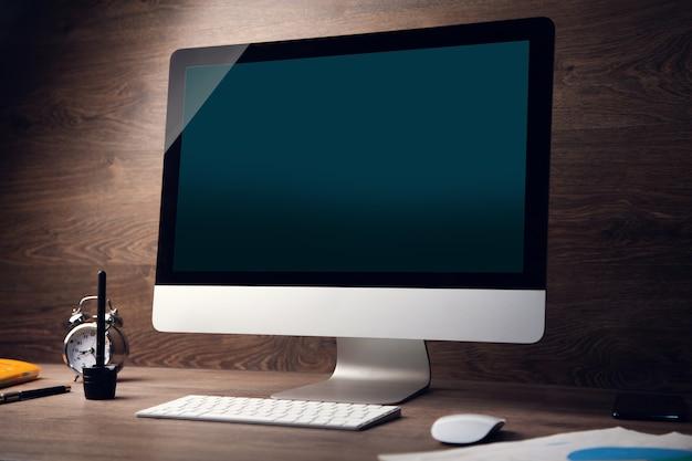 作業中の木製の机の背景にコンピューター