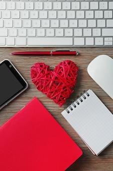 赤い籐のハート、ノートブック、木製のテーブルに携帯電話を備えたコンピュータ周辺機器