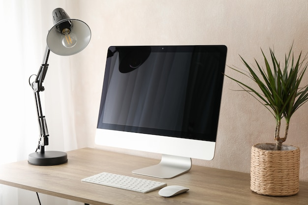 コンピューター、植物、木製のテーブルの上にランプ。職場の部屋