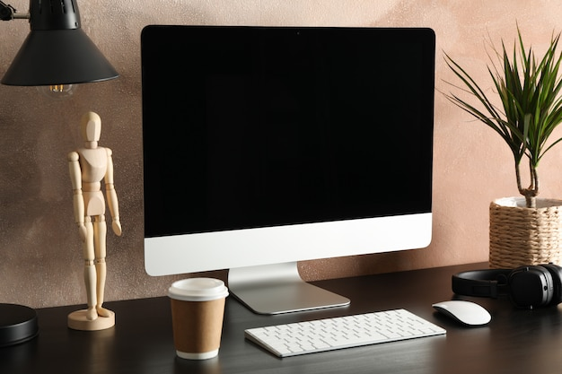 Computer, plant and wood man on wooden table. workplace room