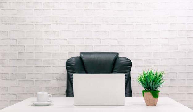 검은 의자와 흰색 벽이있는 흰색 책상에 컴퓨터, planta 및 커피 잔