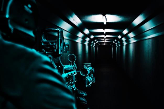 Компьютерный игрок стоит в коридоре и целится в коллиматорный прицел. смешанная техника
