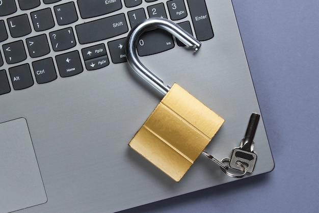 Концепция защиты компьютера, интернет-безопасность. ноутбук и замок на фиолетовой бумаге