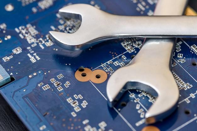 Концепция ремонта компьютера, гаечный ключ на материнской плате крупным планом
