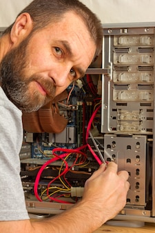 Computer repair. a man with a beard fixing the system unit