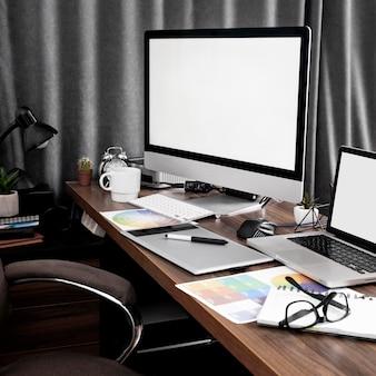 컬러 팔레트가있는 사무실 작업 공간의 컴퓨터 화면 및 노트북