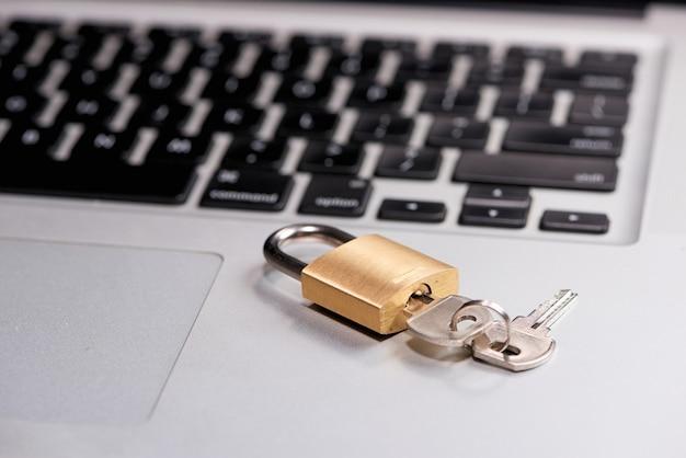 コンピュータのセキュリティとデータ保護の概念。ロックされたロックとキーが付いたラップトップ。