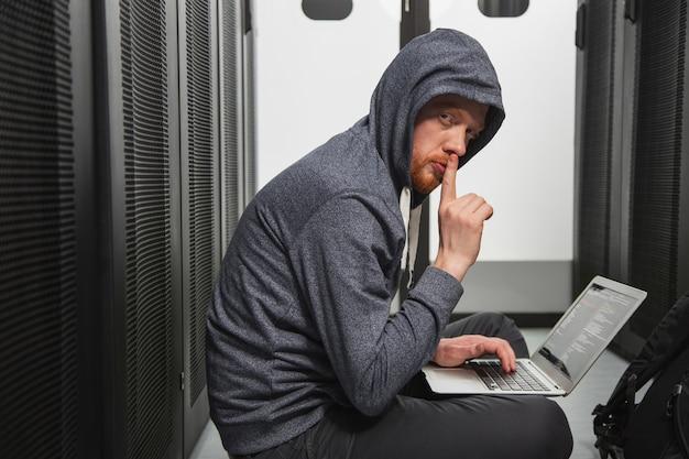 컴퓨터 보안. 시스템을 크래킹하는 동안 손가락을 보여주는 손재주있는 남성 해커