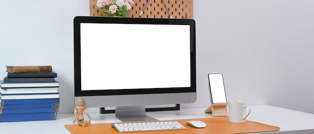 Computer, smart phone, books and office supplies on white desk in modern office.