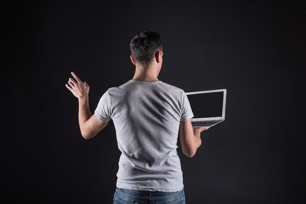 Computer software. confident nice pleasant man holding a laptop and looking it its screen while setting up the computer