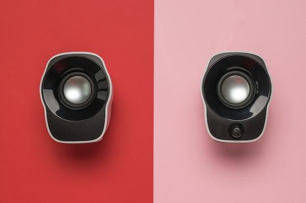 赤とピンクの背景にコンピューターのスピーカー。音声再生装置。