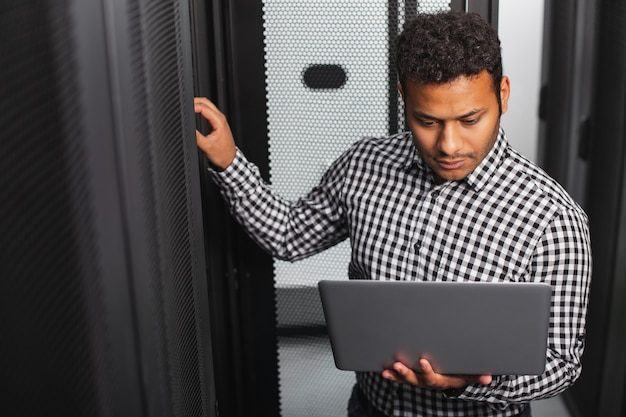 Computer system. top view of concentrated it guy using laptop and looking at screen