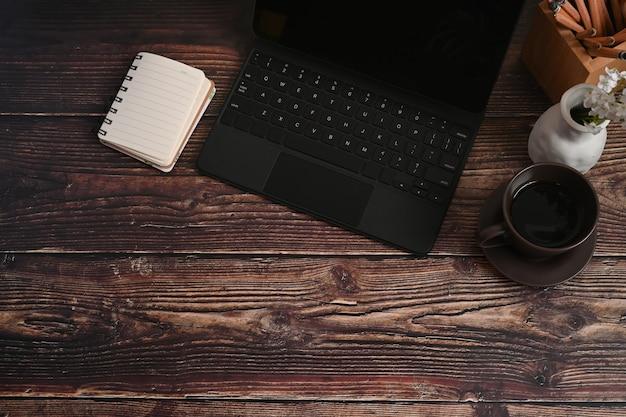 Таблетка, тетрадь и кофейная чашка компьютера на деревянном столе.