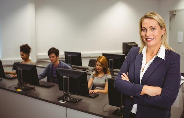 Учитель компьютера, улыбаясь на камеру со скрещенными руками