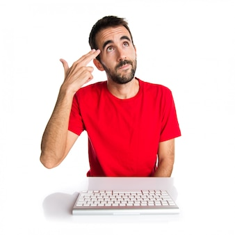 Computer technician working with his keyboard making suicide gesture