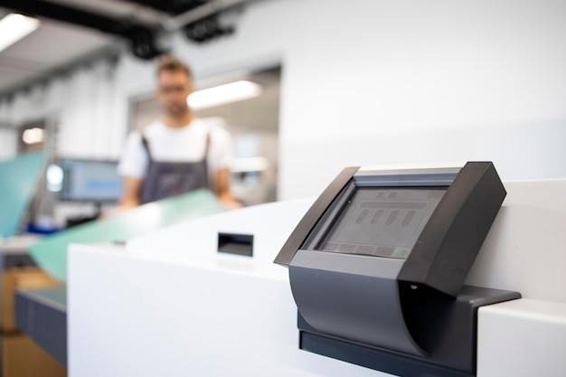 인쇄소에서 기계와 작업자를 도금하는 컴퓨터.