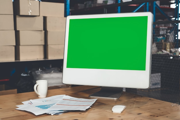 Computer with green screen display in warehouse storage room