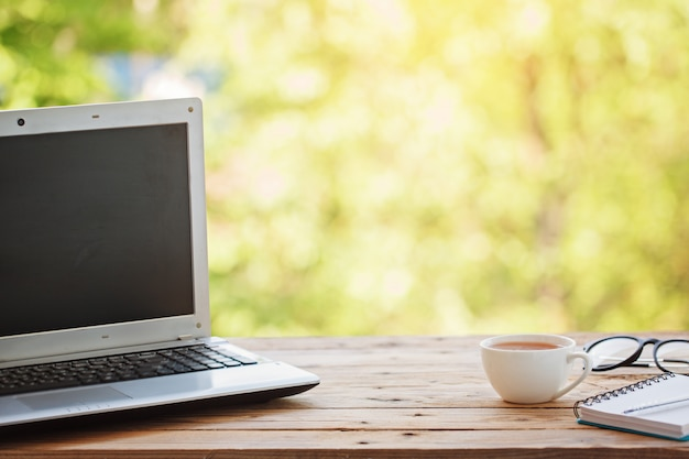 Computer with notebook, glasses and cup of tea or coffee on wooden table and nature background