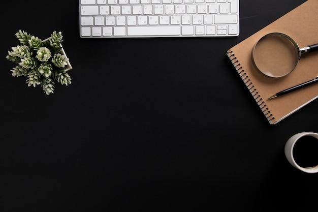 メモ帳とオフィスの黒いテーブルの上のコーヒーとコンピューター