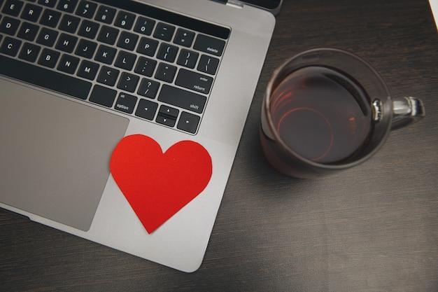 테이블에 붉은 마음으로 컴퓨터를 닫습니다.