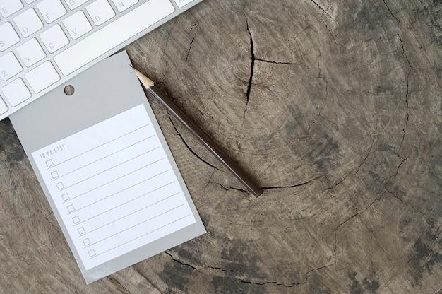 木製の背景に鉛筆と白のcomputerkeyboardでリストを行う空白のリマインダー。