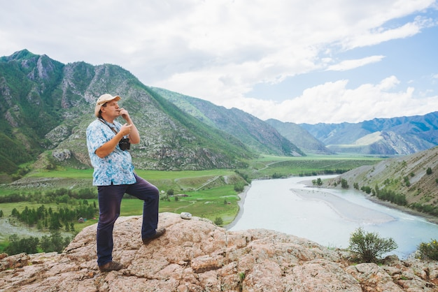 Радостный шальной турист в шляпе на утесе играя на comus против долины среди горной реки и гигантских гор.