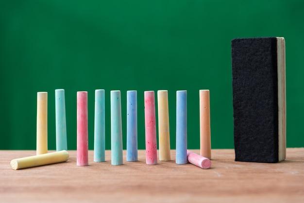 Мел в различных цветах и кисть на столе с зеленым фоном, обратно в школу con