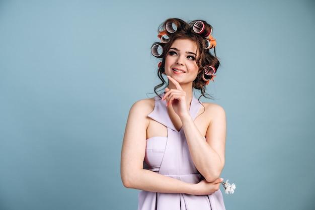 髪にカーラーをつけた、想像力に富んだ魅力的な女性が目をそらします。青い背景、コピースペース、テキストの場所で隔離。