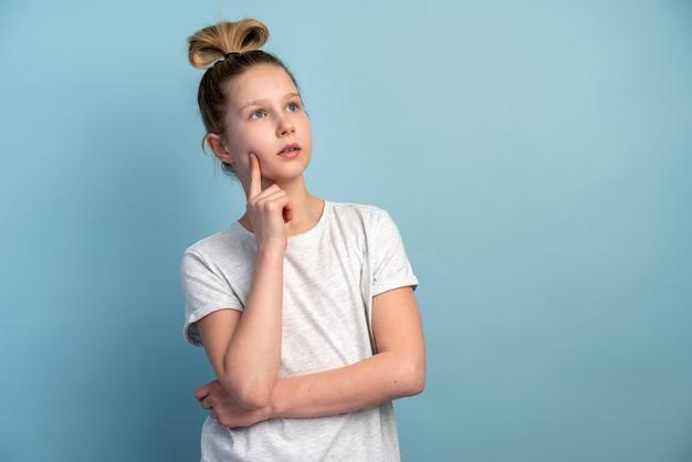 青い壁に白いtシャツを着た10代の少女を想像