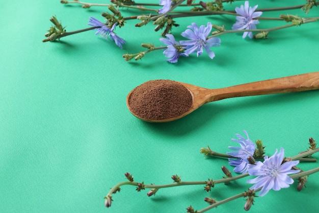 Концентрат и цветы цикория на зеленом фоне. здоровый травяной напиток, заменитель кофе, место для текста