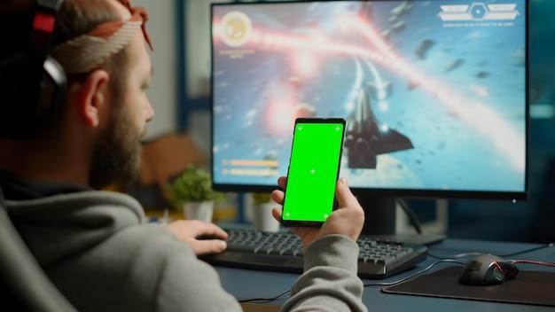強力なコンピューターストリーミングオンライン競争でゲームをプレイしながら、緑色の画面で携帯電話を持っているゲーマーを集中させて、クロマキーディスプレイをモックアップします。シューティングゲームをプレイする分離されたデスクトップを使用しているプレーヤー