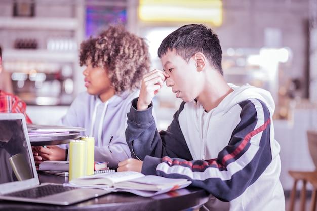 Сконцентрируйтесь на задаче. красивый азиатский мальчик сидит в полу-положении, думая об обследовании