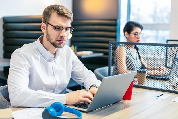Сконцентрируйтесь на задаче. красивый мужчина брюнетка сидит на своем рабочем месте, проверяя свой почтовый ящик