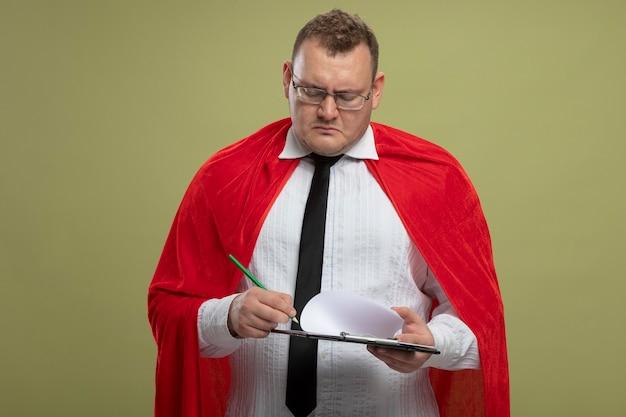 복사 공간 올리브 녹색 벽에 고립 된 펜으로 클립 보드에 쓰는 안경을 쓰고 빨간 망토에 집중된 성인 슬라브 슈퍼 히어로 남자
