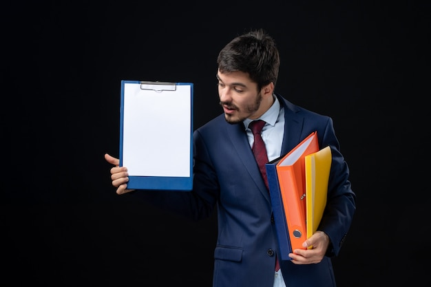 Concentrated adult in suit holding several documents and showing one of them on isolated dark wall