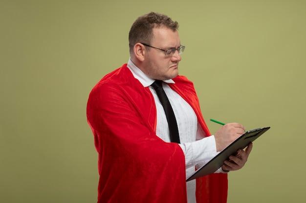 Сосредоточенный взрослый супергерой в красном плаще в очках, стоящий в профиль, пишет в буфер обмена ручкой, изолированной на оливково-зеленой стене