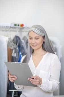 Концентрированная взрослая женщина, стоящая в химчистке, изучает документ в папке в хорошем настроении