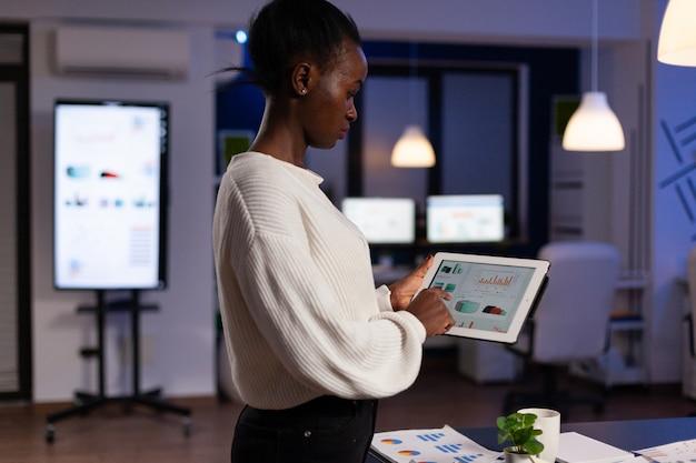 タブレットコンピューターを保持している集中アフリカ系アメリカ人のエグゼクティブマネージャー