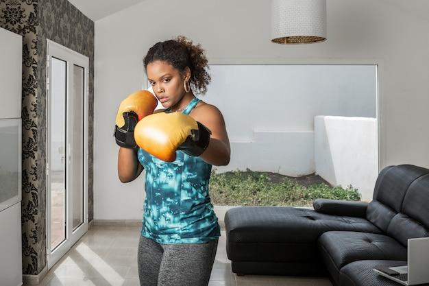 自宅でトレーニング中にパンチを行うアクティブウェアとボクシンググローブに集中したアフリカ系アメリカ人のスポーツウーマン