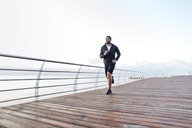 Концентрированный афро-американский молодой спортсмен работает на пирсе утром